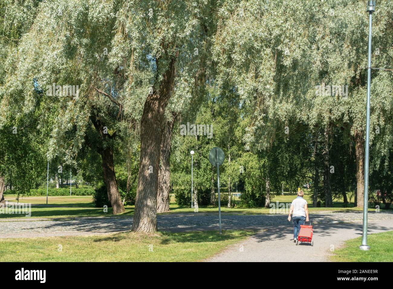 Old lady with luggage in a Park in Hämeenlinna Finland Stock Photo
