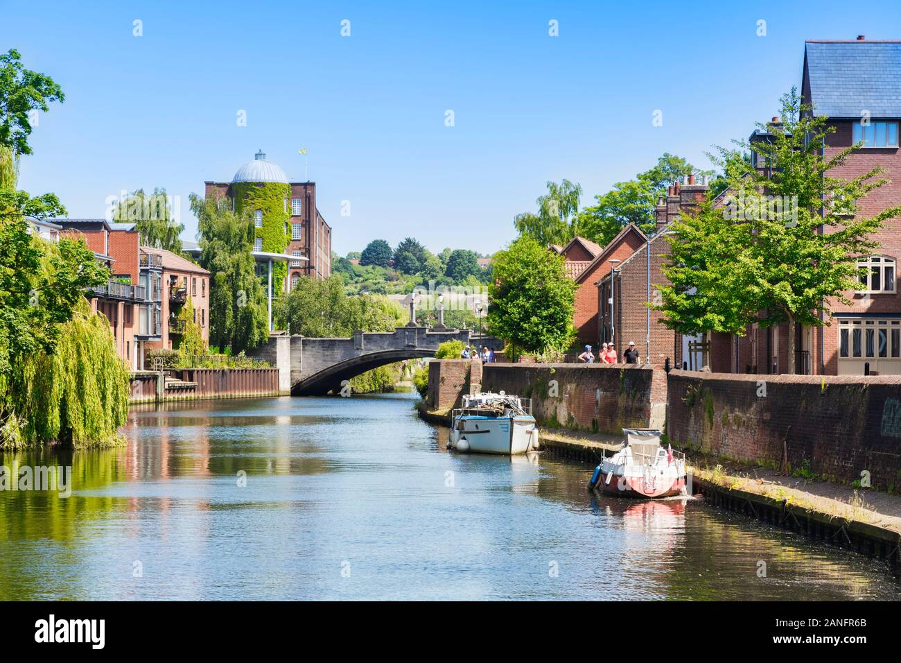 29 June 2019: Norwich, Norfolk, UK - Tourists walking beside the River Wensum on a sunny summer day. Stock Photo
