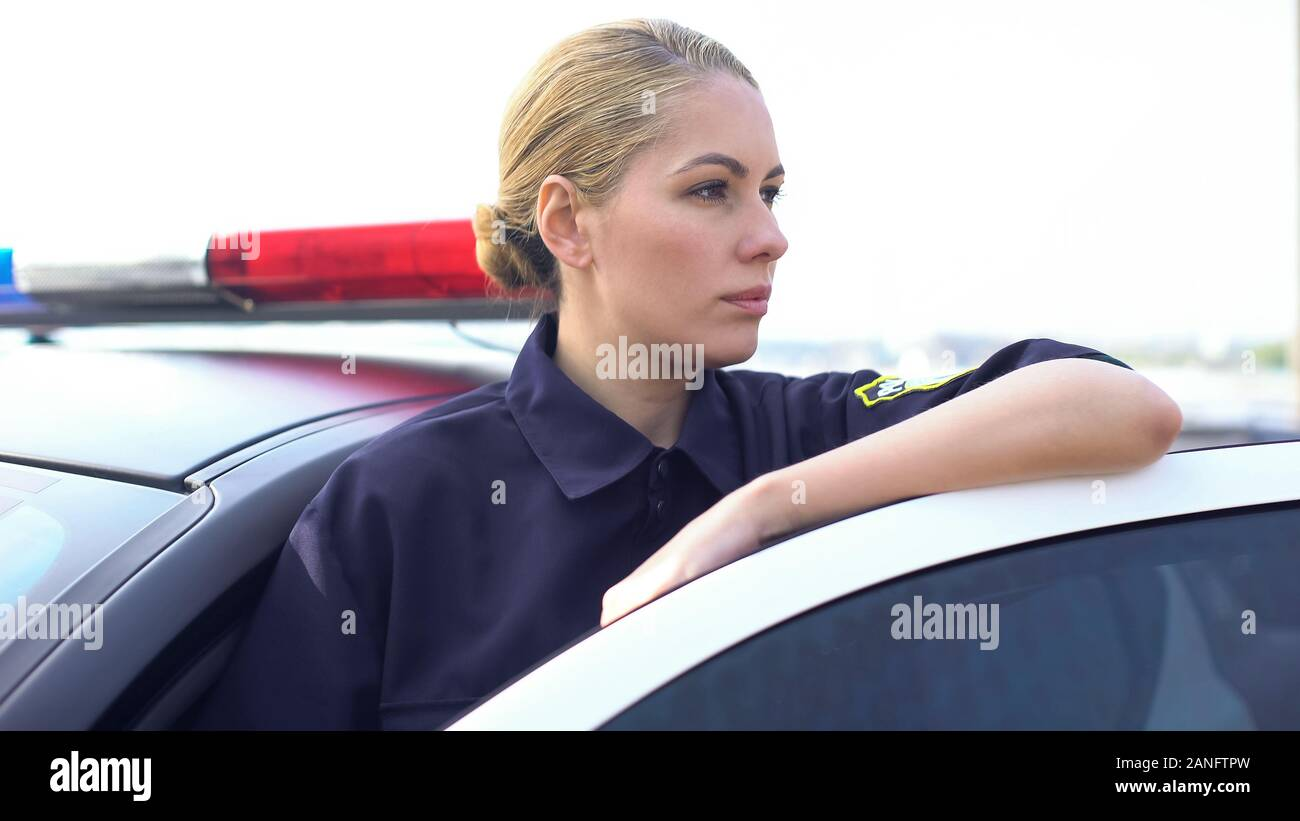 Brave policewoman standing near patrol car, protection of public order in city Stock Photo
