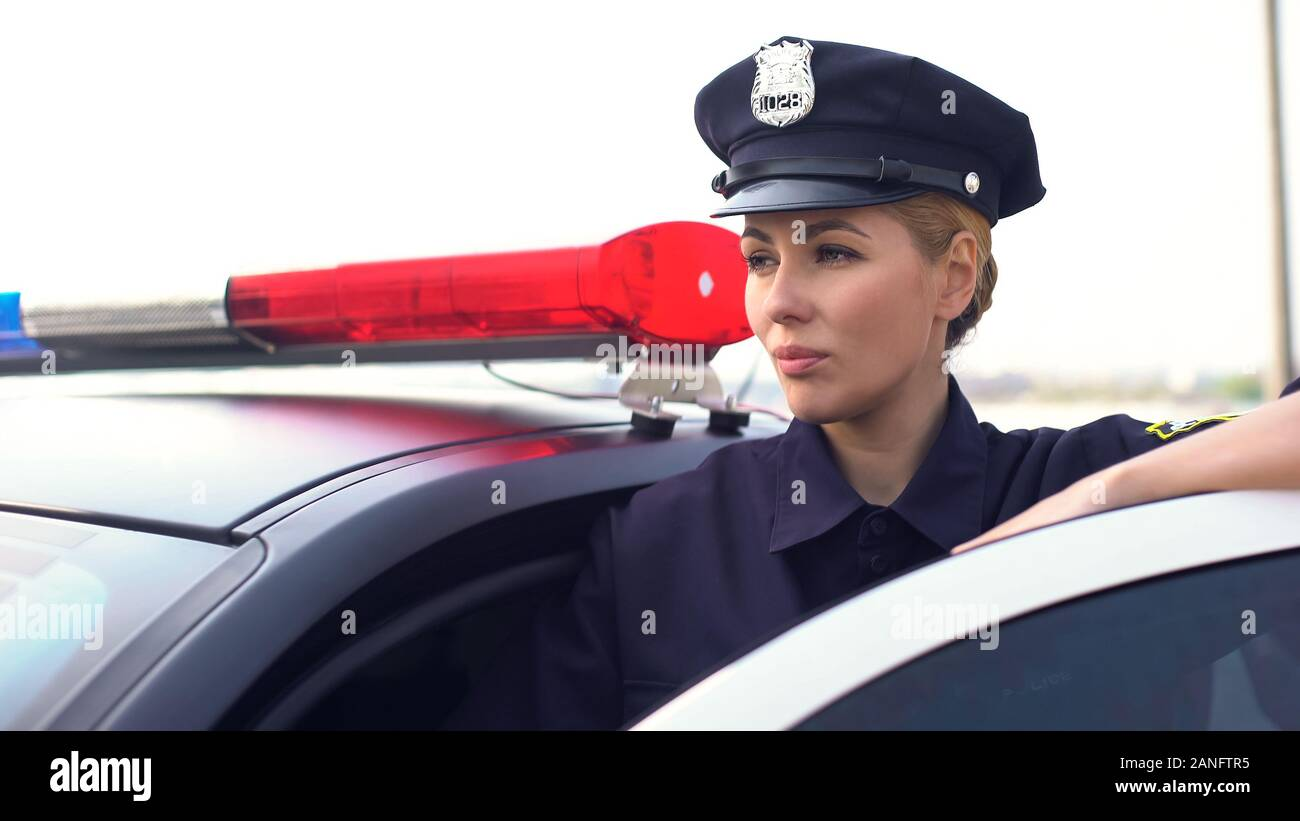Strong lady in police uniform standing near patrol car, protecting law and order Stock Photo