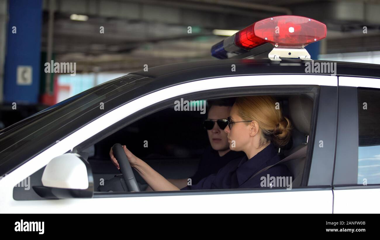 Male and female cop driving police car to crime scene, patrolling law in city Stock Photo