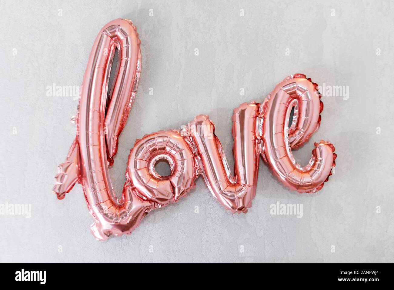love word from pink inflatable balloon on grey concrete background the concept of romance valentines day love rose gold foil balloon 2ANFWJ4