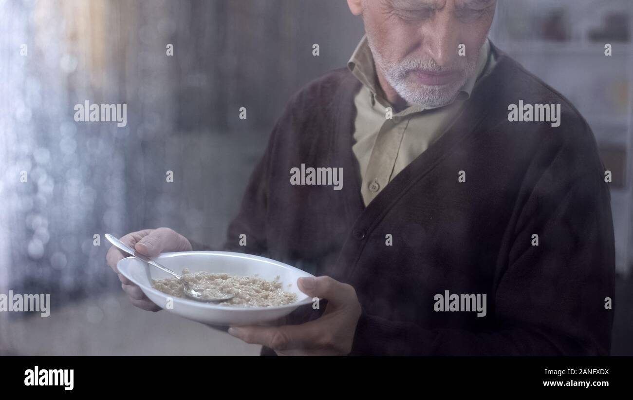 Retired man holding plate with disgusting tasteless oatmeal, lack of money Stock Photo