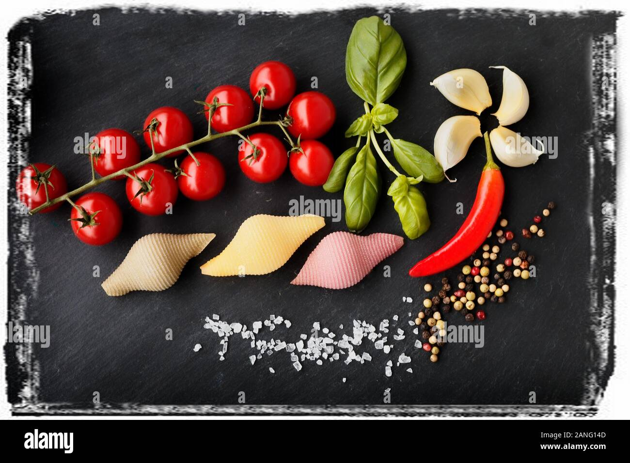 Pasta with vegetables ingredients on a black stone for an Italian pasta dish Stock Photo