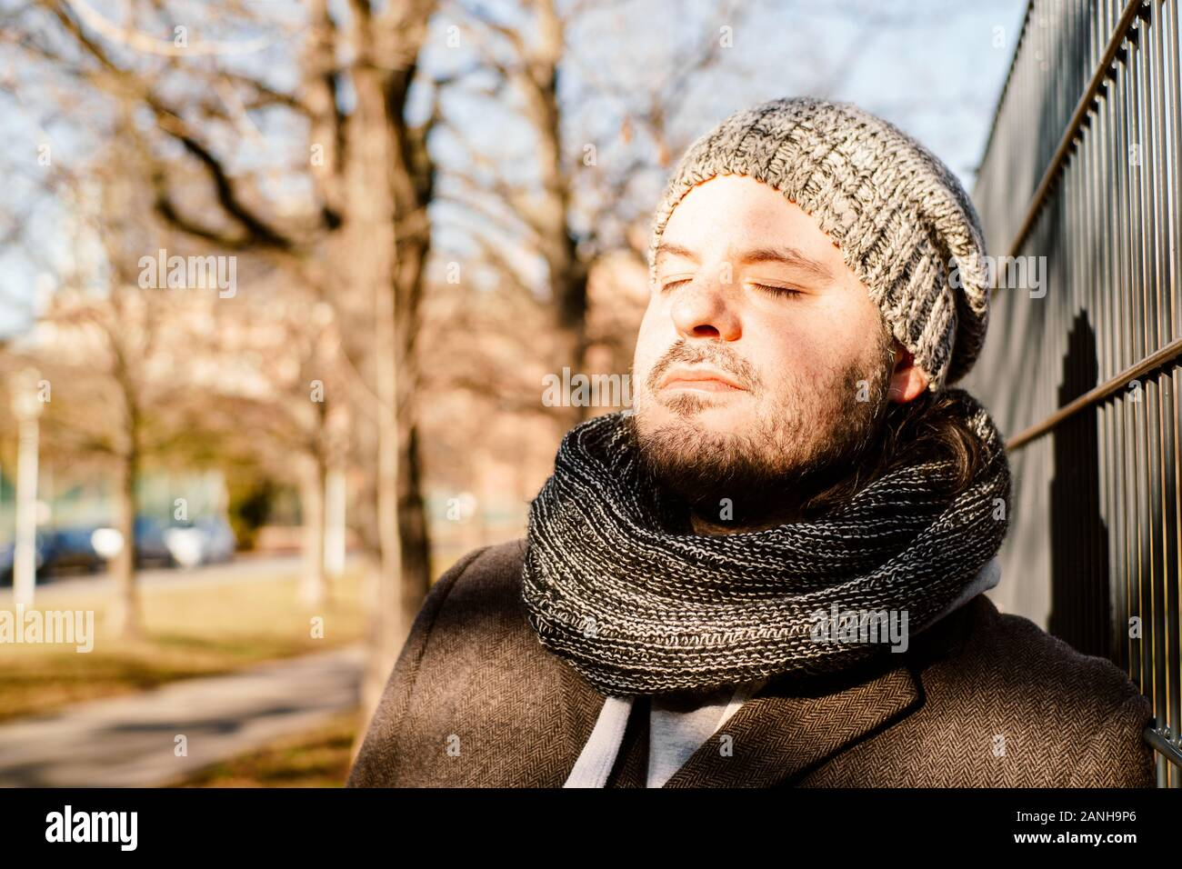 Man leans against a fence outside and enjoys the sun in the cold season. Contemplation, serenity and relaxing concept. Stock Photo