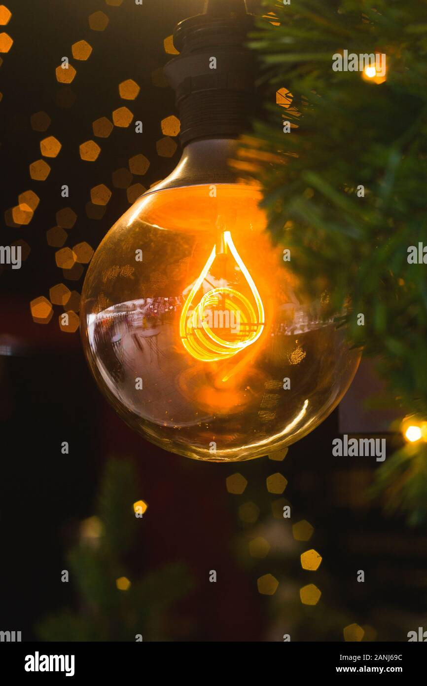 One Large Yellow Incandescent Lamp Among Christmas Tree Branches And Small Lights Stylish Modern Christmas Interior Decoration Stock Photo Alamy