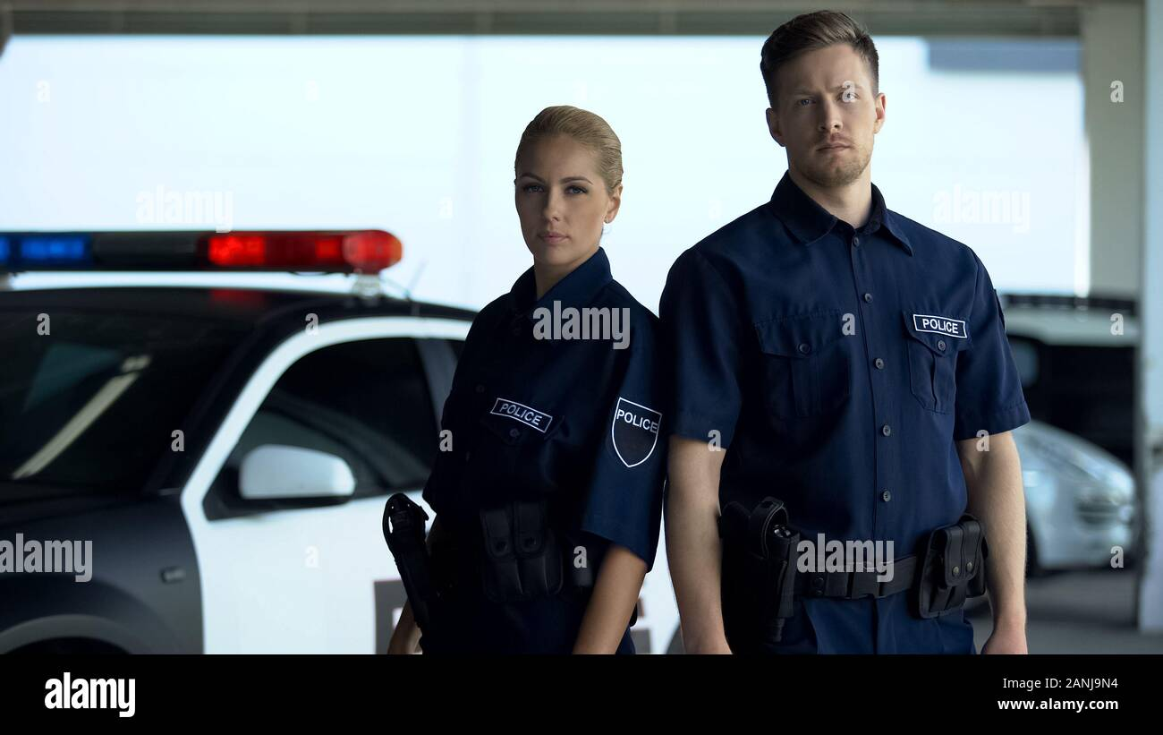 Confident woman and man police officers standing near patrol car, on duty Stock Photo