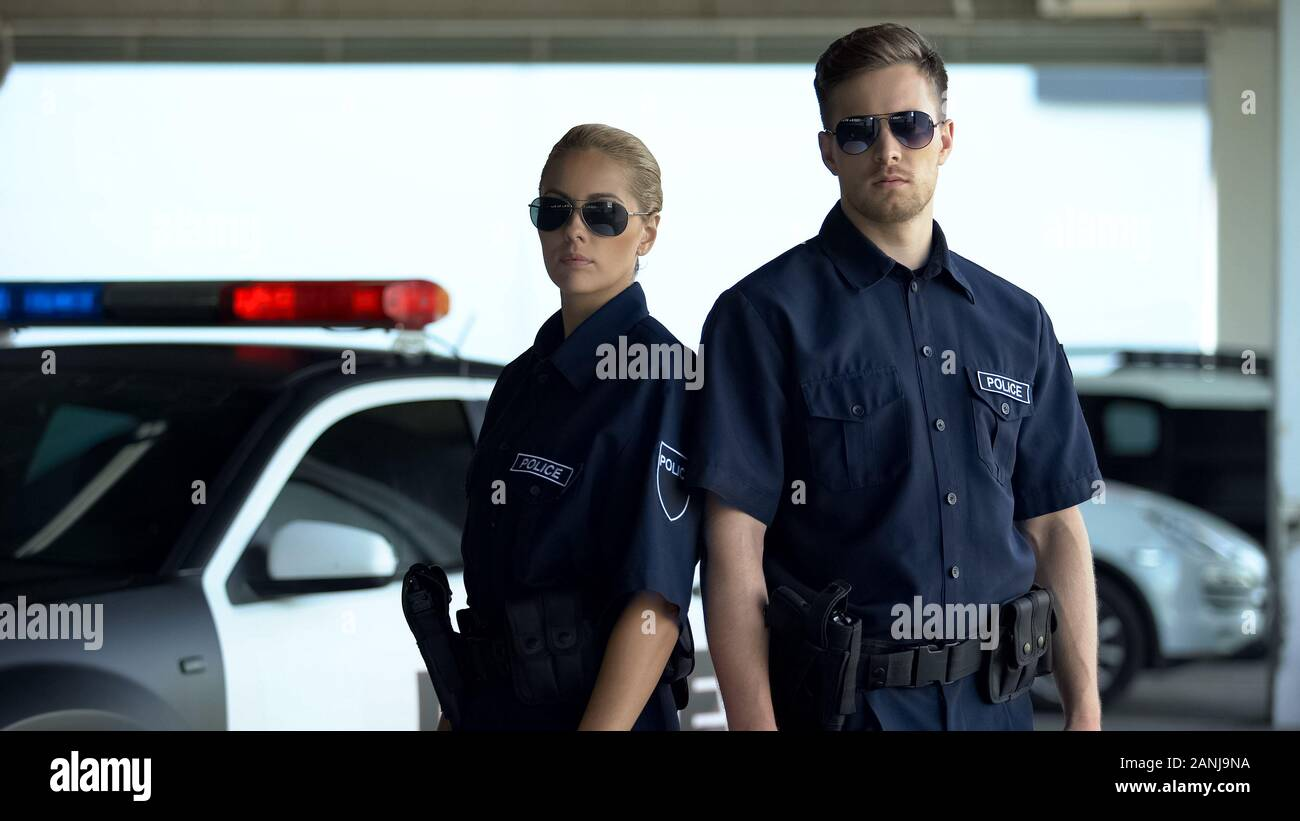 Confident policewoman and man in sunglasses standing near patrol car, on duty Stock Photo