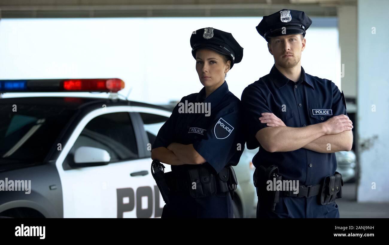 Two brave policemen in uniform and service cap posing near patrol car, order Stock Photo