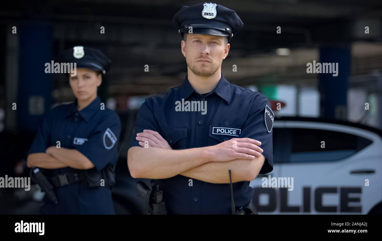 Confident male and female police officers in uniform standing near patrol car Stock Photo
