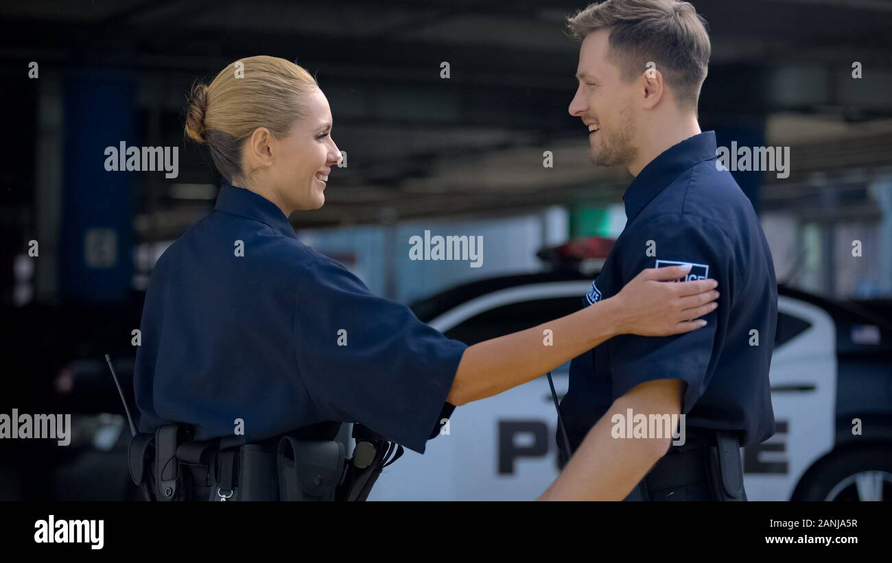 Police mates greeting each other standing near patrol car, ready to carry duties Stock Photo