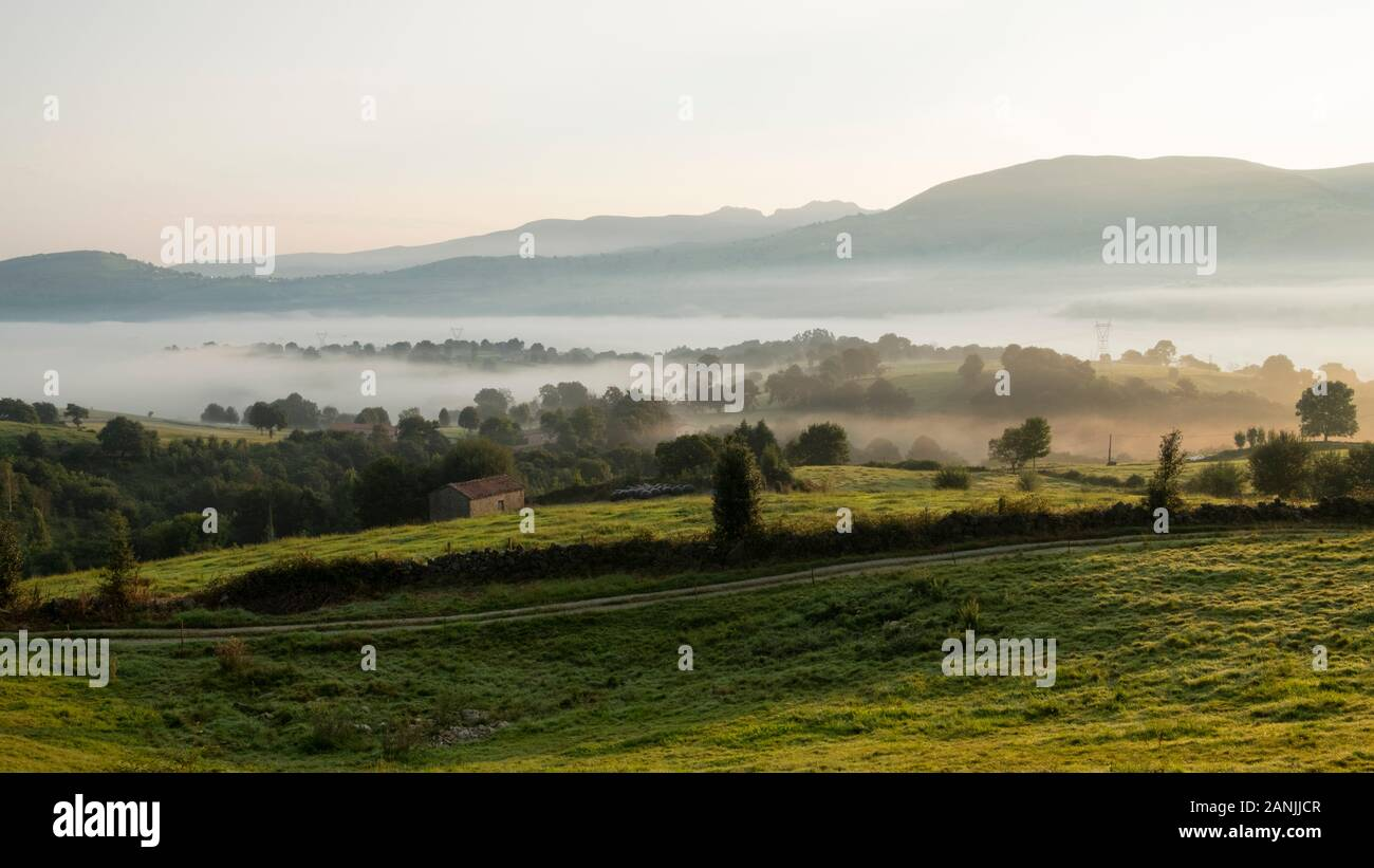 Traditional cabaña pasiega hut and pastures in Valles Pasiegos countryside covered with mist at sunrise (Tezanos, Villacarriedo, Cantabria, Spain) Stock Photo