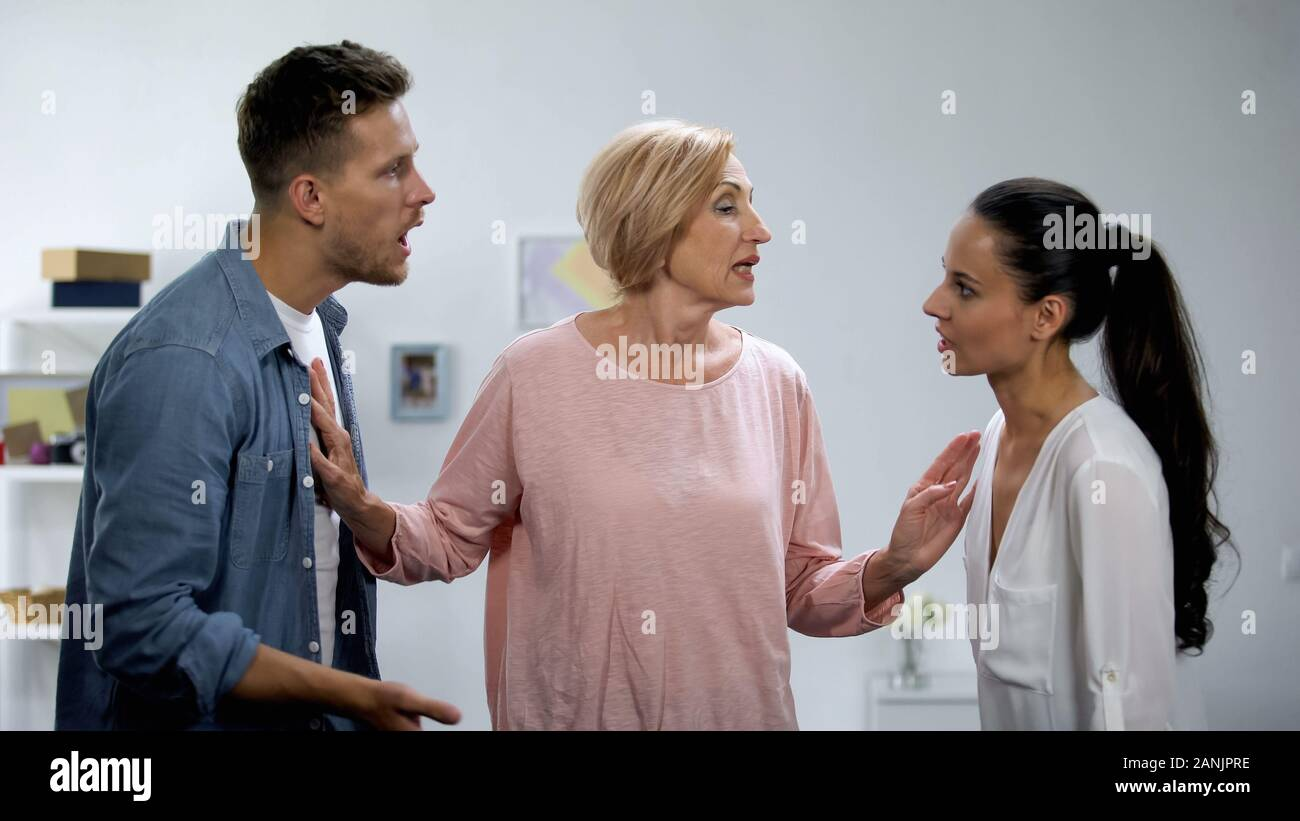 Mother-in-law trying to reconcile quarrelling couple, family conflict, support Stock Photo