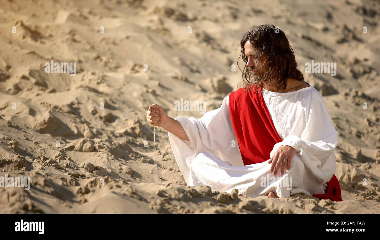 Philosopher pouring sand from hand in desert, reflecting on life and time Stock Photo