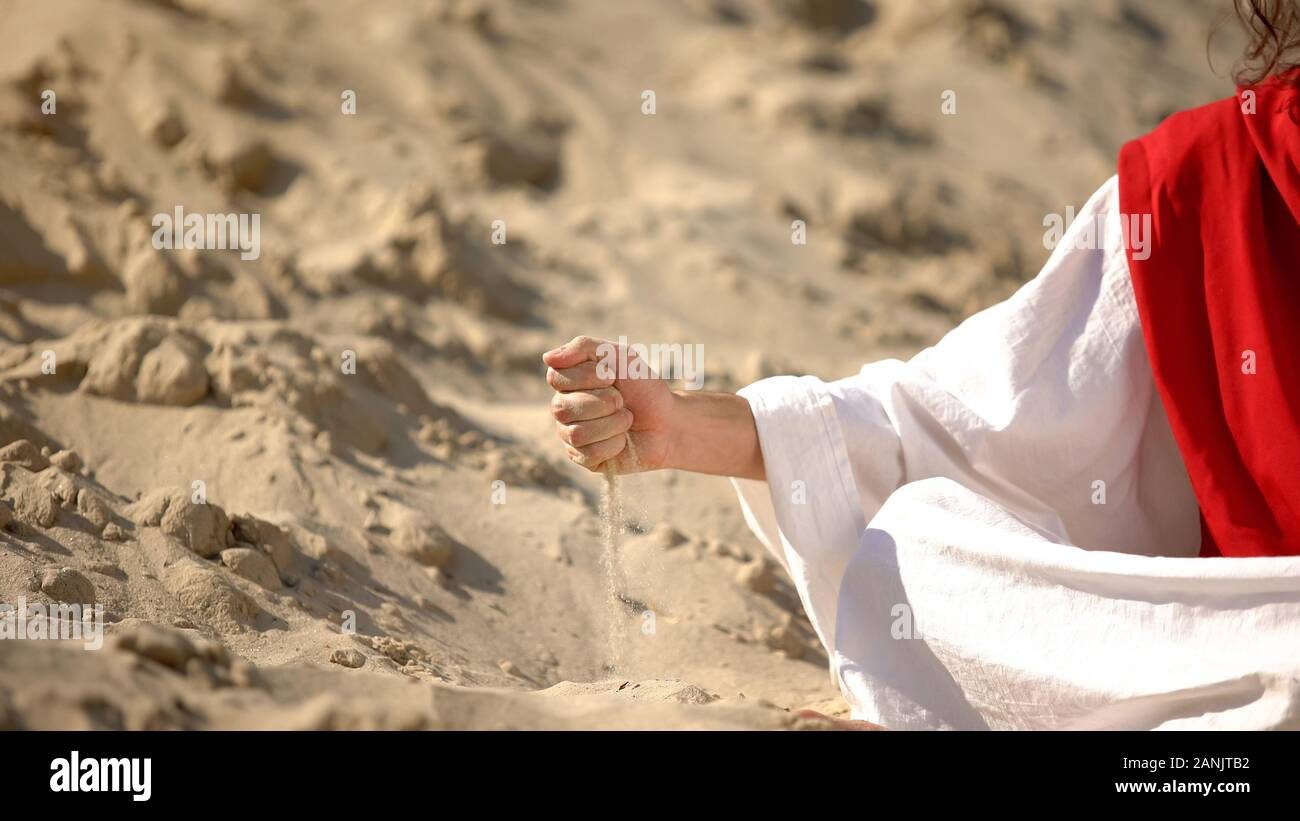 Male hand in robe pouring sand, symbol of passing life, time is running out Stock Photo
