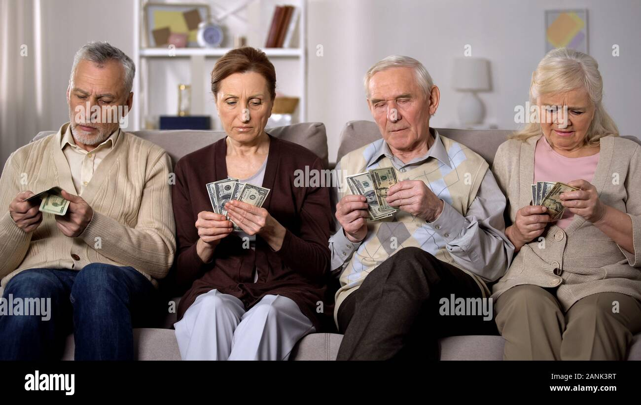 Poor aged couples counting dollars at home, lack of money, social insecurity Stock Photo