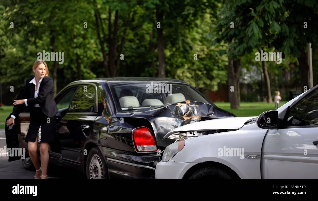 Shocked female driver getting out car looking at wrecked cars on road,  safety Stock Photo - Alamy