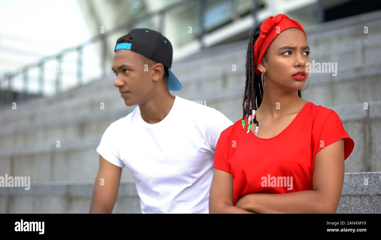 Mixed-race couple sitting separately offending at each other after quarrel Stock Photo