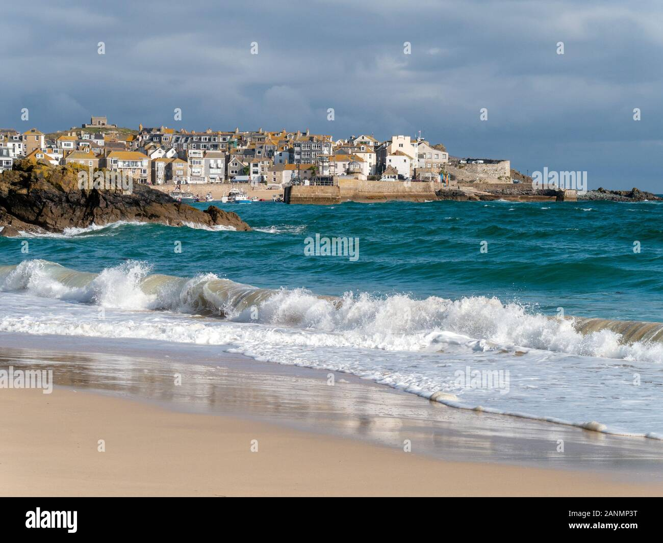 The seaside town of St. Ives a seen over the waves and sea surf  of sandy Porthminster Beach, Cornwall, England, UK. Stock Photo