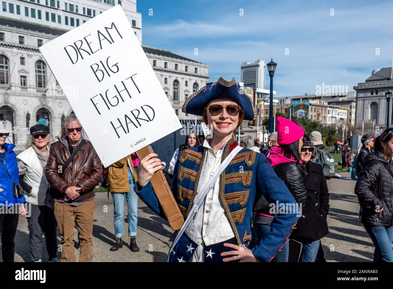 """San Francisco, USA. 18th January, 2020. The 4th annual Women's March San Francisco, California. A woman dressed in 1776 costume holds a sign reading, """"Dream big, fight hard,"""" an Elizabeth Warren campaign slogan. Stock Photo"""