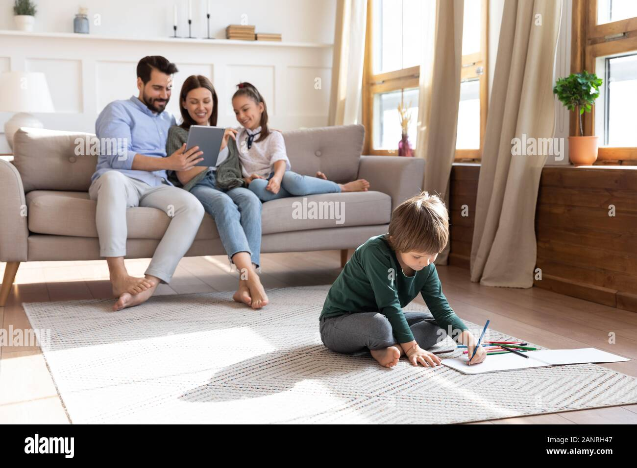 Young family with small kids relax in living room Stock Photo - Alamy