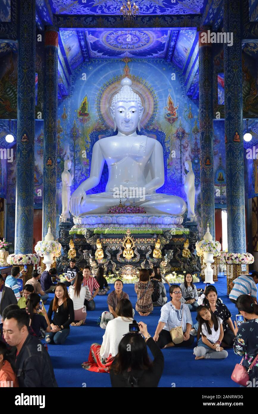 Wat Rong Seur Ten, also known as the Blue Temple, with visitors having their pictures taken in front of the statue of the Buddha, Chiang Rai, Thailand Stock Photo