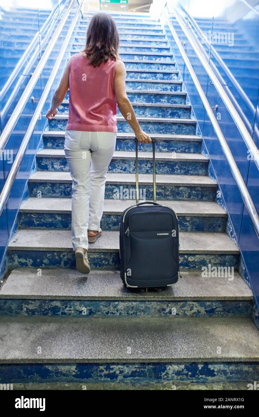 Woman walking up the stairs of a train station. Concept of travel Stock Photo