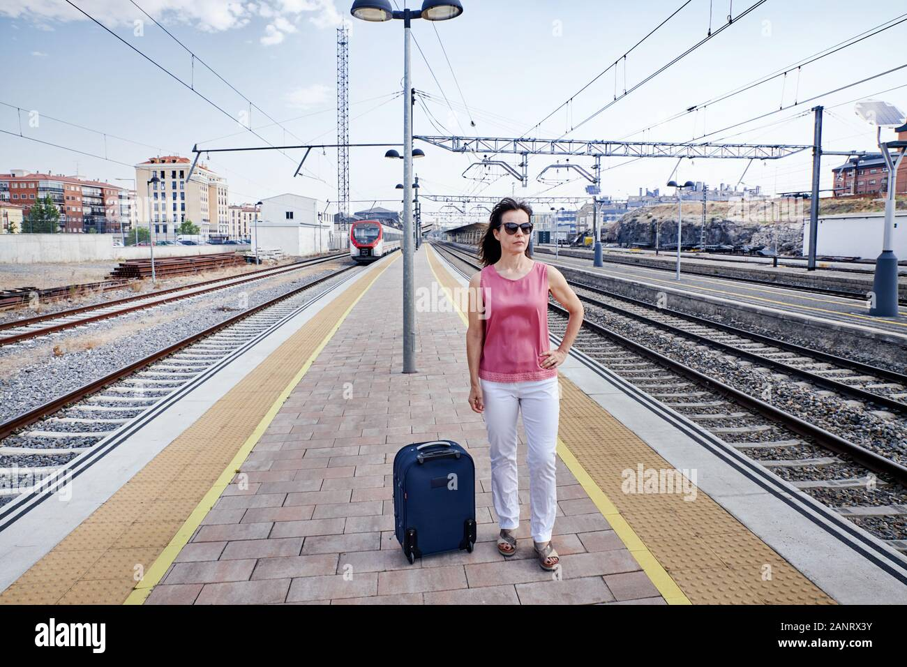 Traveler woman walking and waits train on railway platform. Concept of travel Stock Photo