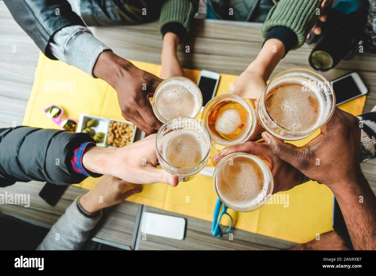 Group of friends enjoying a beer glasses in english pub restaurant - Young people cheering at vintage bar - Friendship, happy hour and party concept - Stock Photo