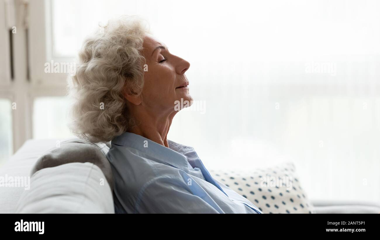 Head shot profile peaceful older woman relaxing on couch Stock Photo