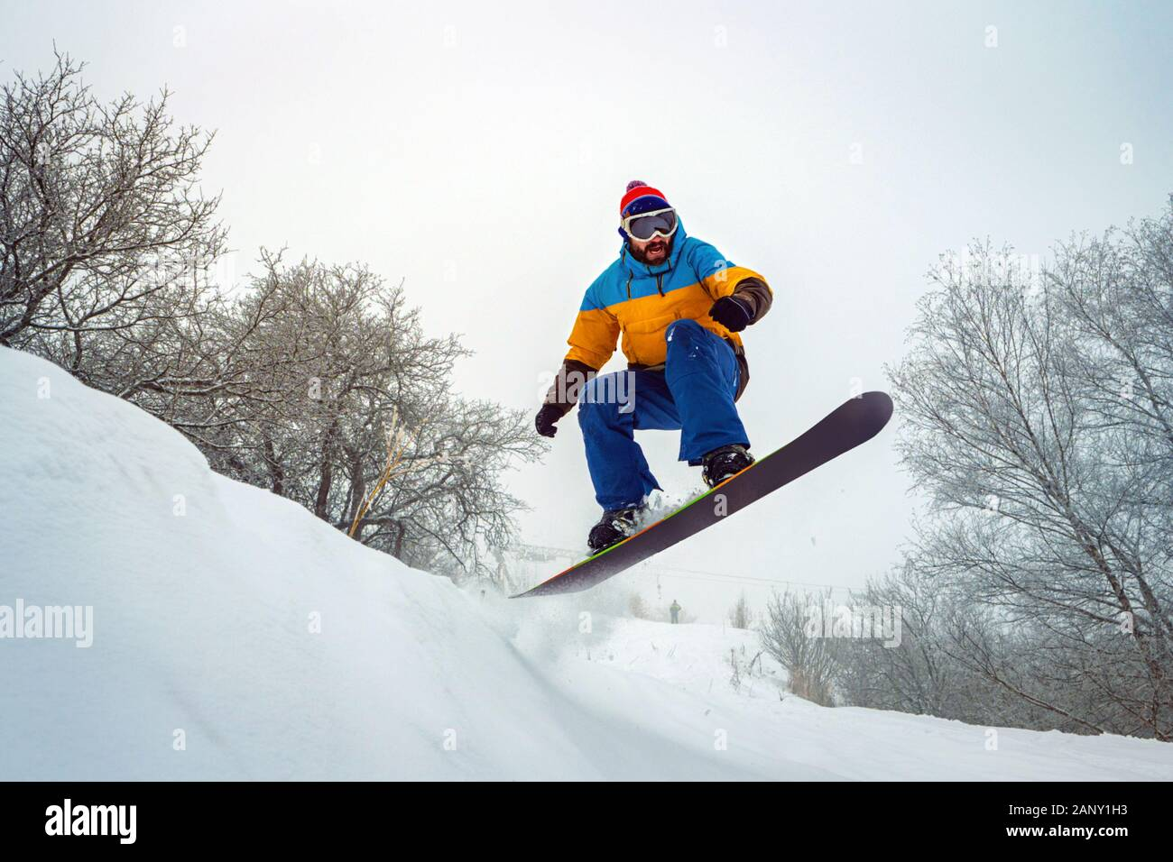 The guy is snowboarding. He jumps out of a snowy hill. Snowboarding in the fresh snow. Winter fun Stock Photo
