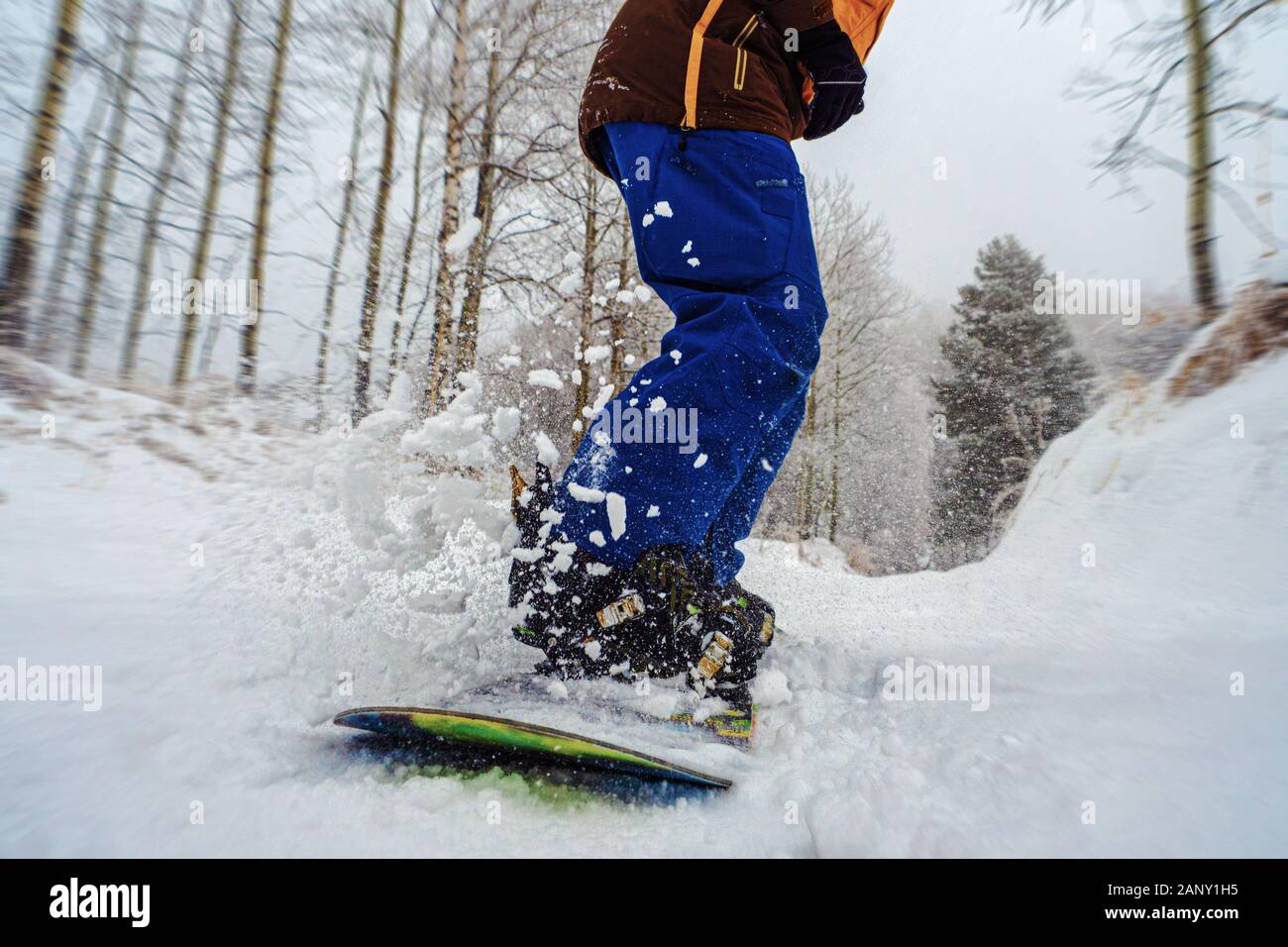 Close-up of a snowboard is glides with snow splashes. Snowboarder rides in the fresh snow. Stock Photo
