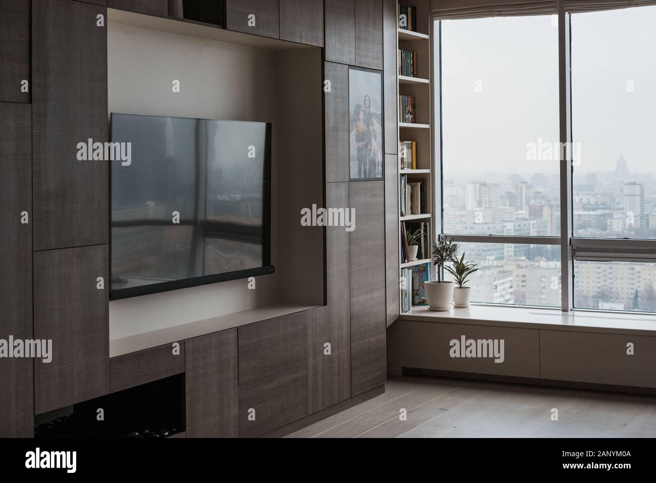 Furniture in a modern style, a large TV screen in the modern living room with panoramic windows. Comfortable living space. Stock Photo