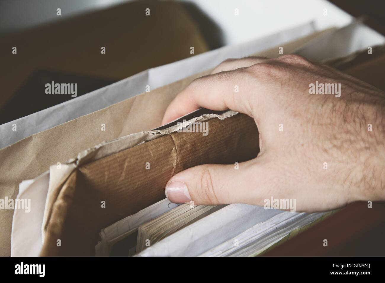 Closeup shot of a person grabbing cardboard out of a box Stock Photo