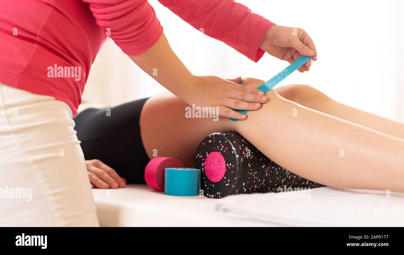 Physical therapist applying kinesio tape on female patient's knee. Close up cropped shot. Kinesiology, physical therapy, rehabilitation concept. Stock Photo