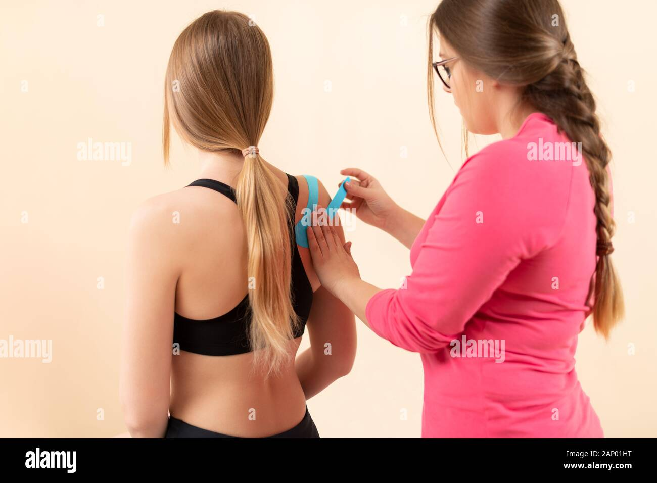 Physical therapist applying kinesio tape on female patient's shoulder. Kinesiology, physical therapy, rehabilitation concept. Rear view. Stock Photo