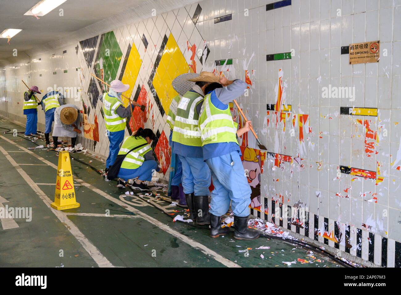 January 20 2020 Hong Kong.  Cleaners removing anti government posters from a Lennon  Wall  in Hang Kou Tsuen Kwan O. Stock Photo