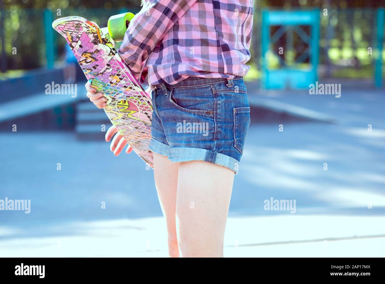 portrait of a little girl, in a plaid shirt, standing with a skateboard, on the playground. Teen girl smiling. Active kids lifestyle Stock Photo