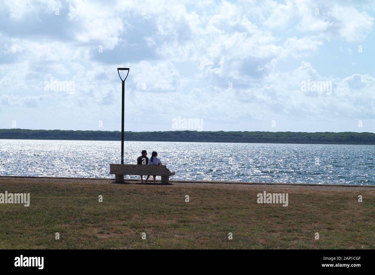 couple sitting on a bench against sun Stock Photo