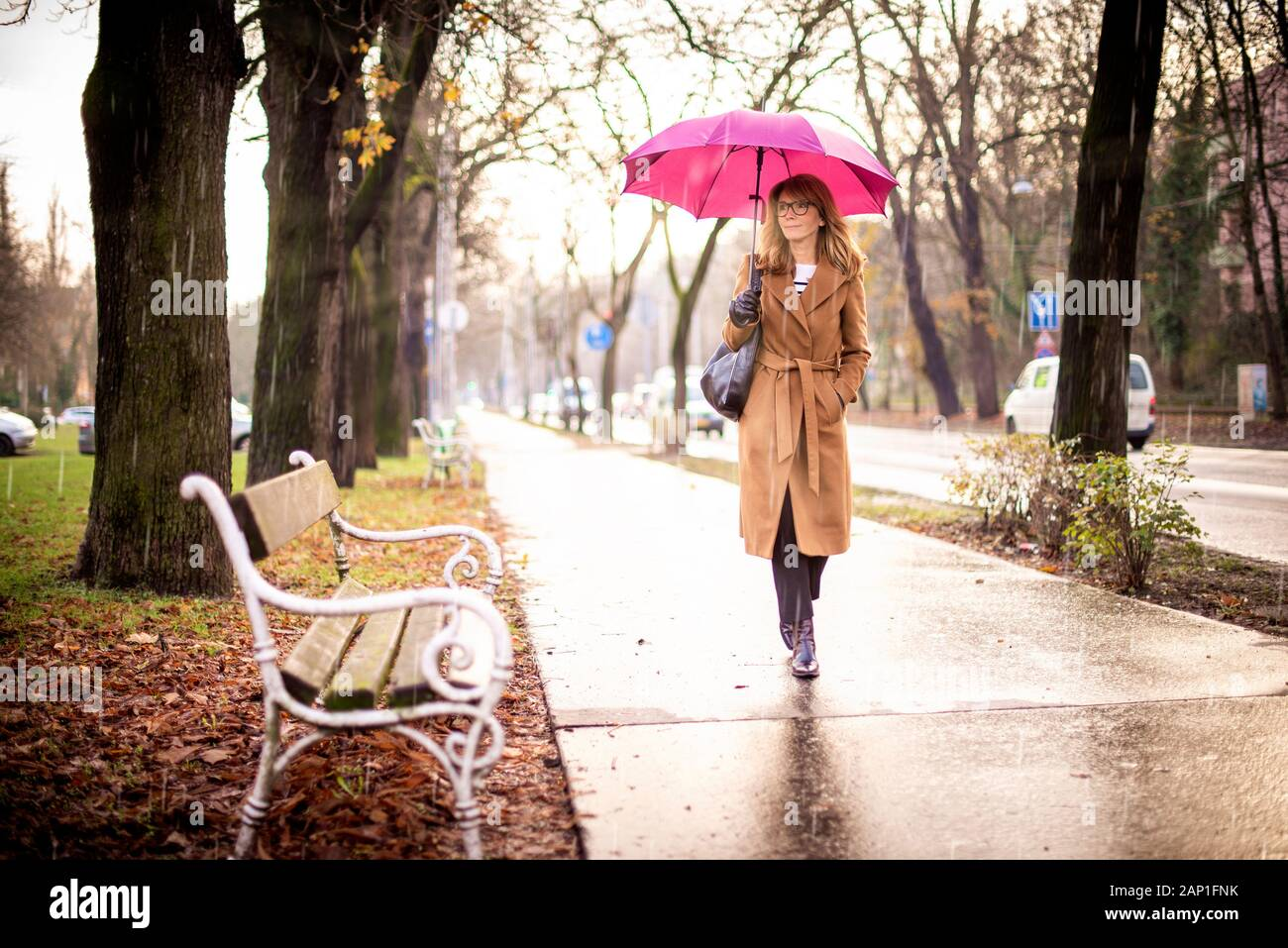 Full length shot of mature woman holding umbrella while walking on the street on a rainy day. Stock Photo