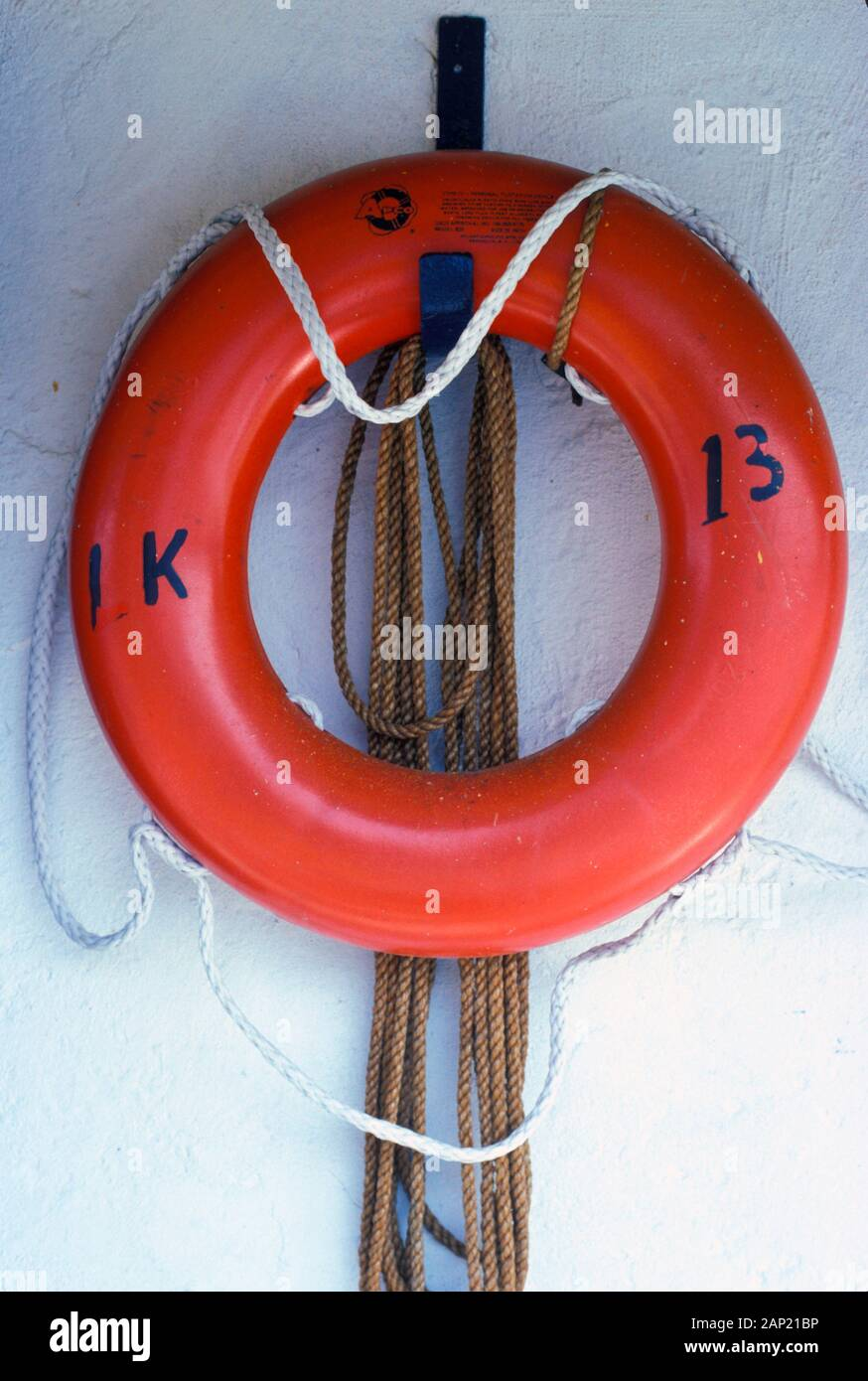 Orange life preserver and rope against a white wall Stock Photo