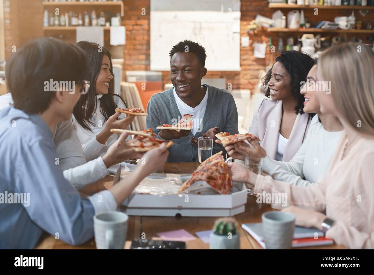Happy people eating lunch at coworking office during break Stock Photo