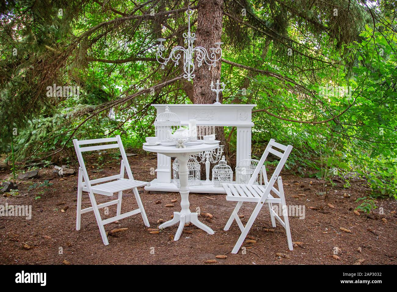 White Outdoor garden furniture. Two wooden chairs and a table in