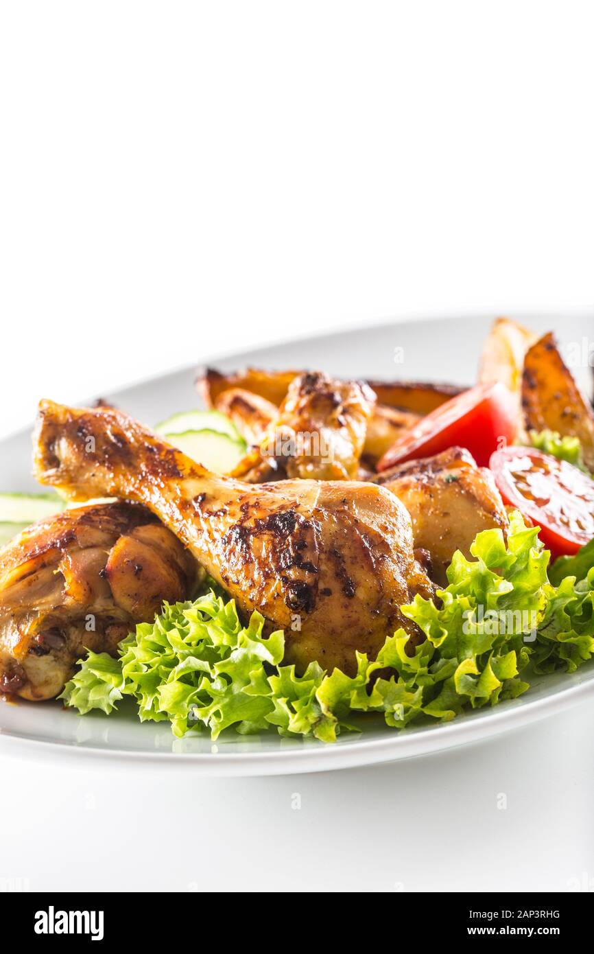 Roasted chicken legs with lettuce salad potatoes and tomatoes isolated on white Stock Photo