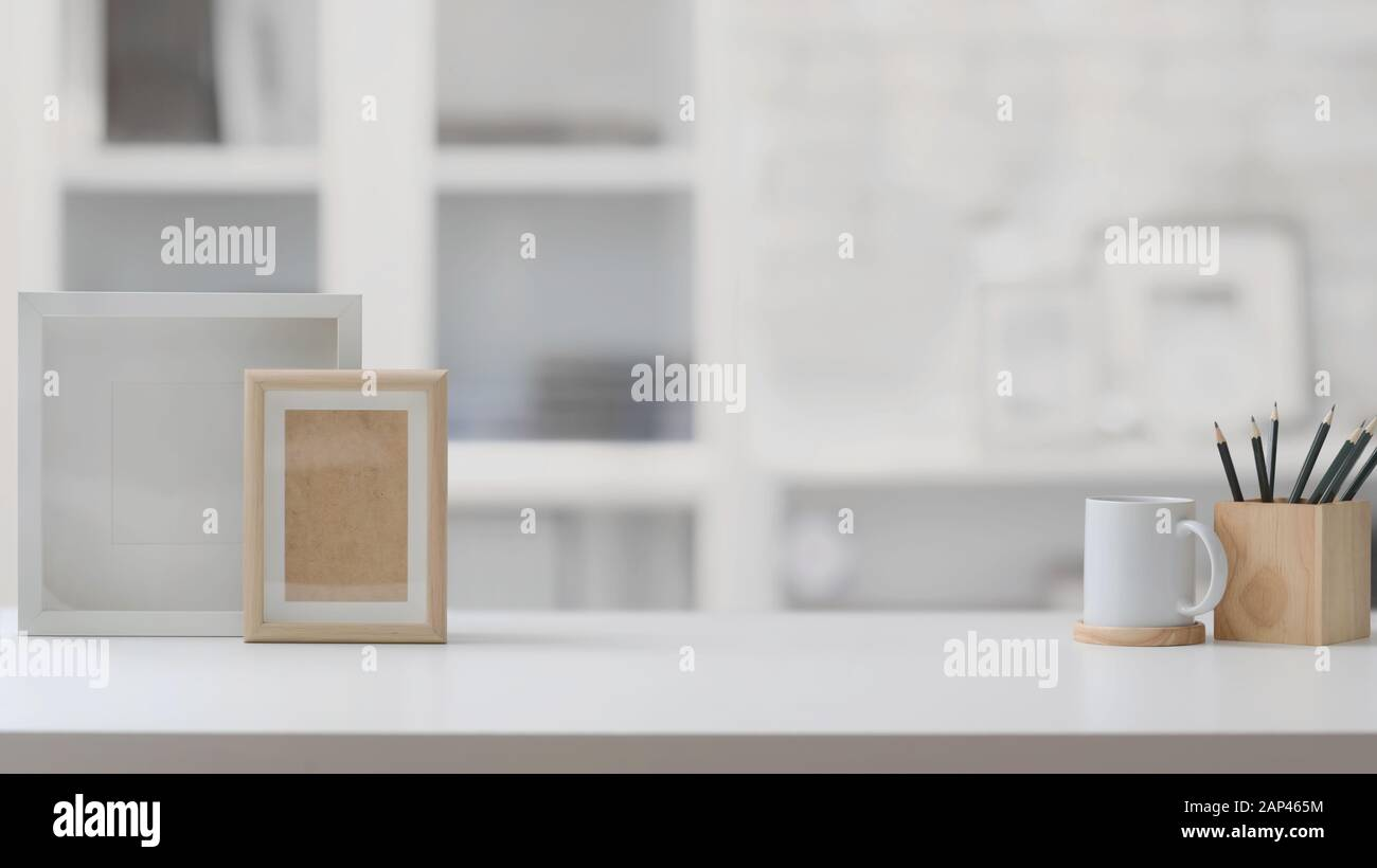 Close Up View Of Stylish Workplace In Blurred Home Office Background With Copy Space Mock Up Frames Pencils And Coffee Cup On White Table Stock Photo Alamy