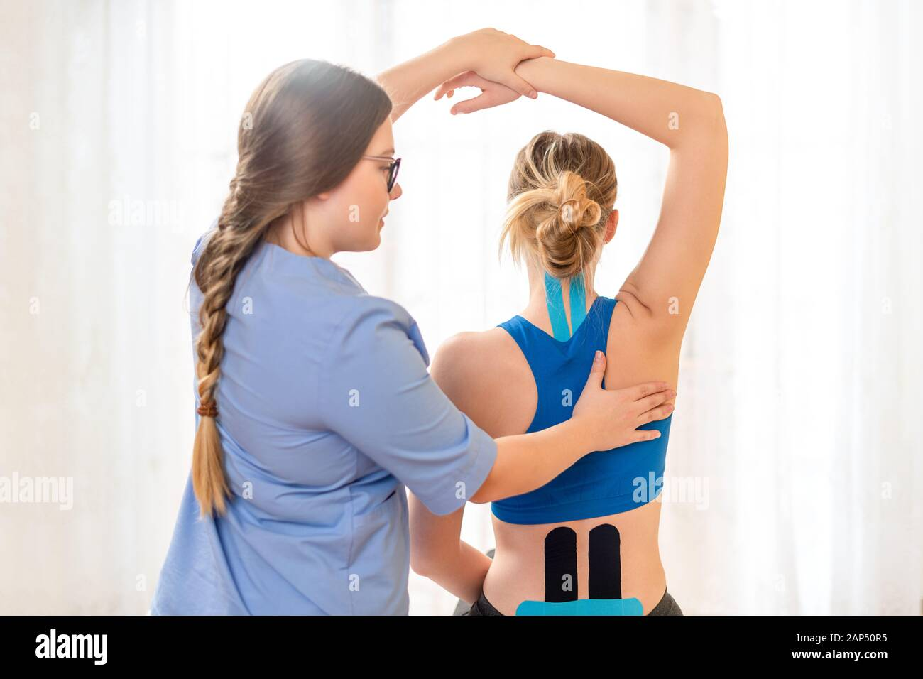 Young female patient wearing kinesio tape on her back and neck exercising with a professional physical therapist. Kinesiology, physical therapy, rehab Stock Photo