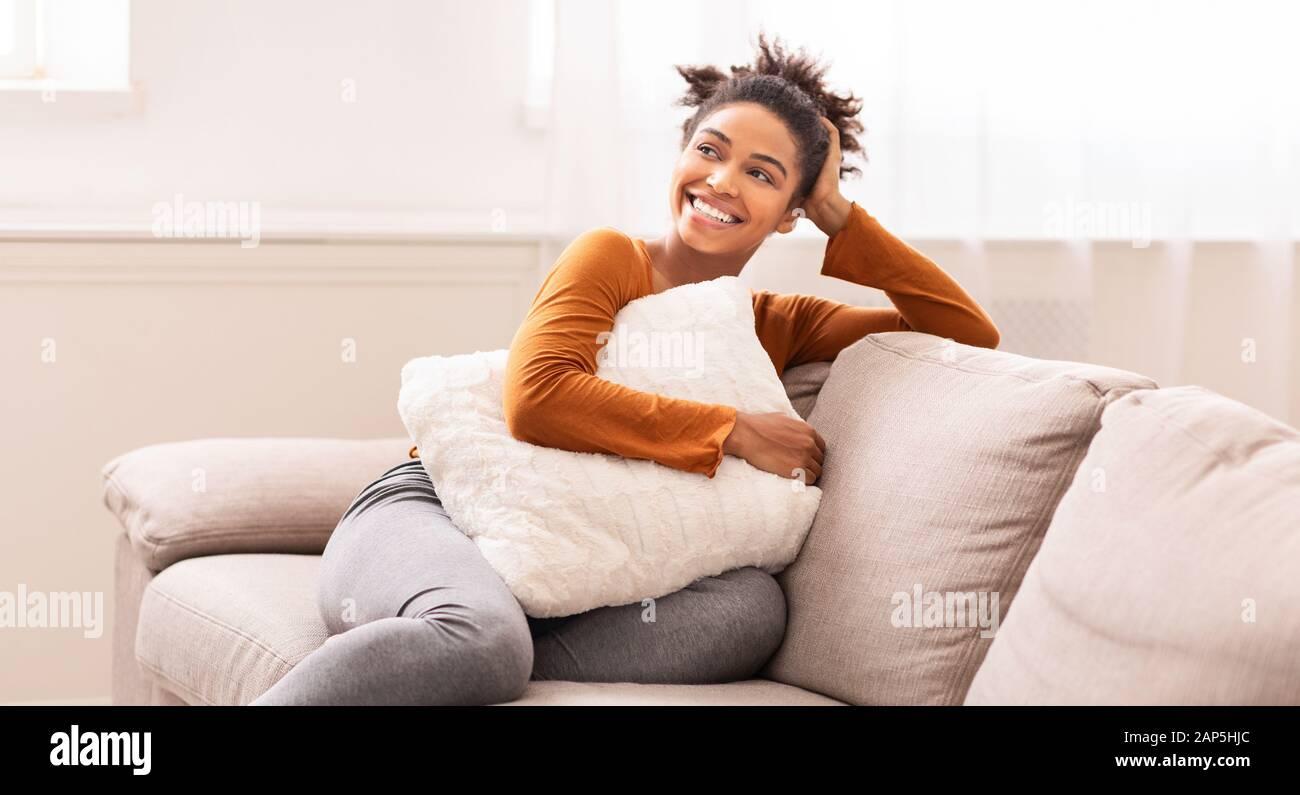 African American Woman Sitting On Sofa Embracing Pillow Indoor, Panorama Stock Photo