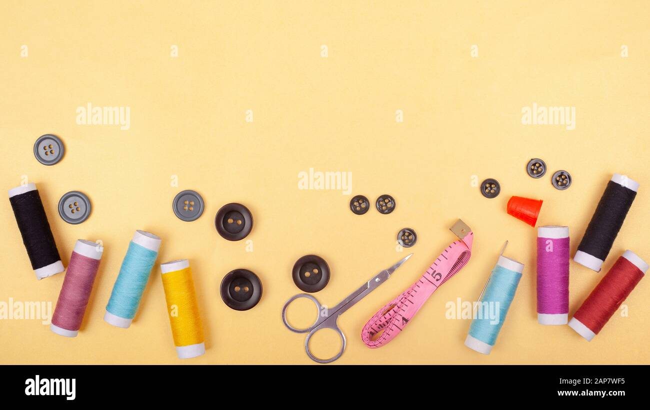 flat lay  Sewing kit accessory or tailor tool workshop .Space for creative design mock up frame. threads, pins, scissors, buttons. Stock Photo