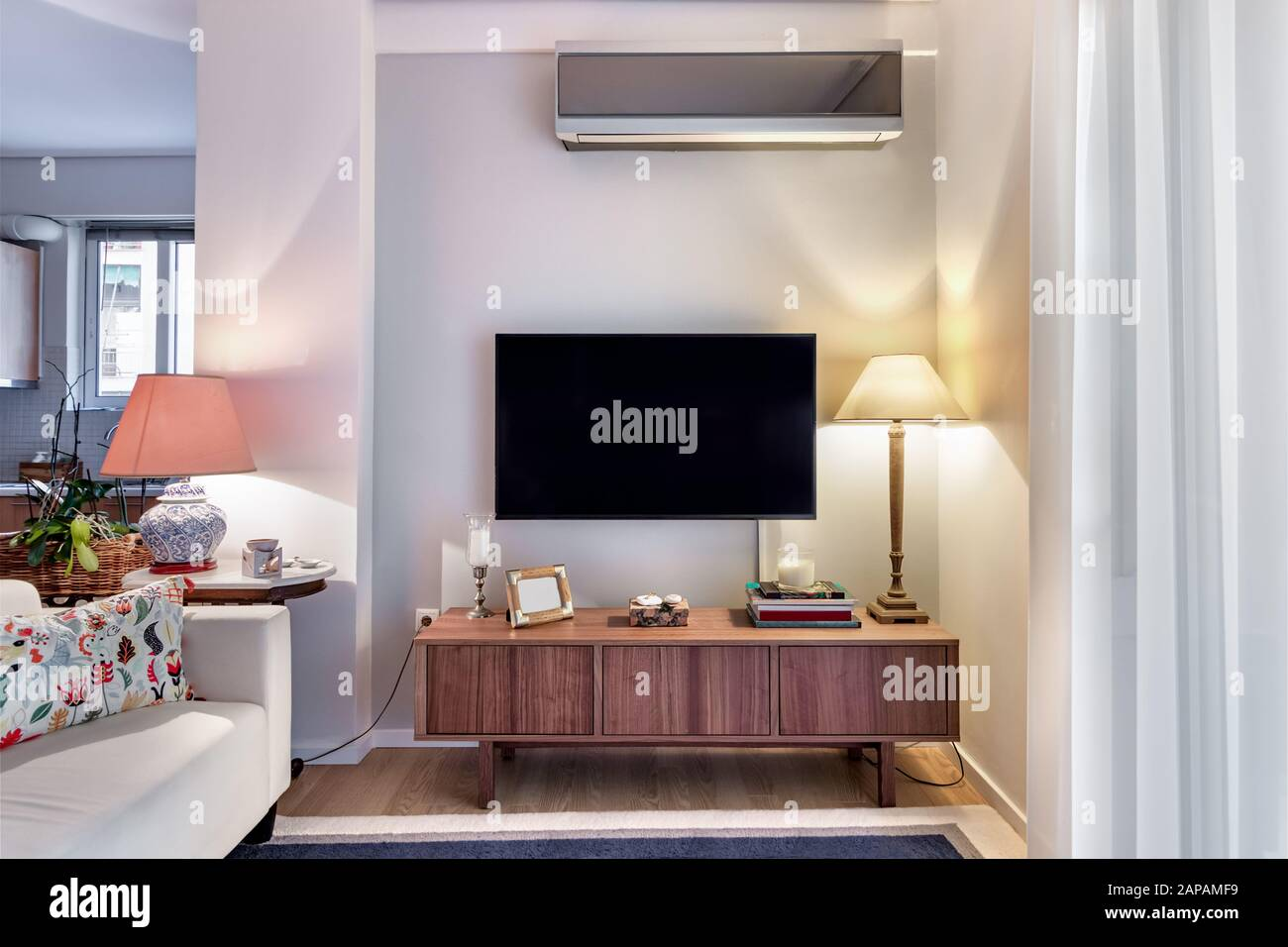 Wooden Cabinet With Flat Tv And Lamps On A Small Living Room Stock Photo Alamy