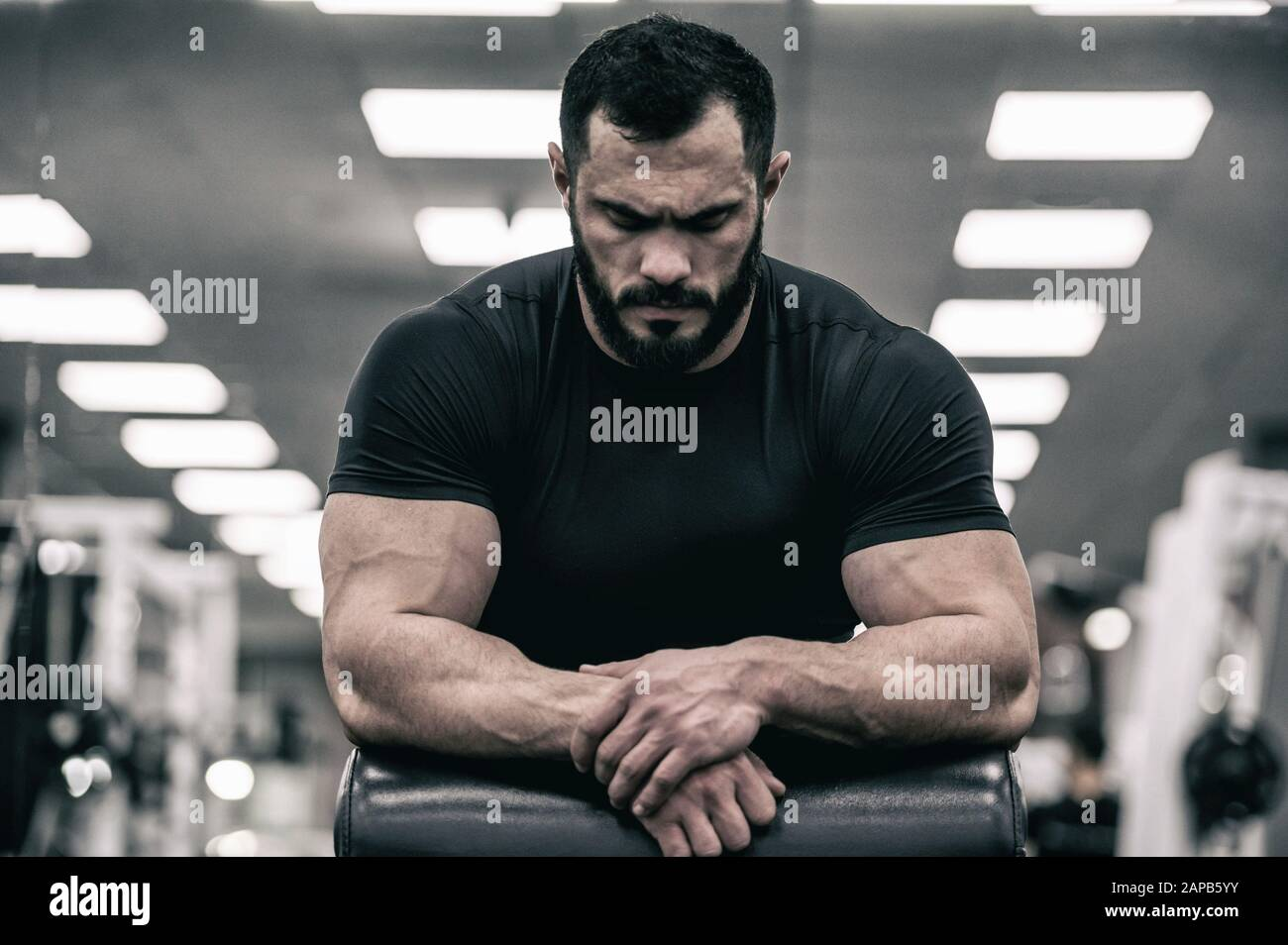 mental mind sport motivation concept of young strong man with beard wearing black jersey concentration relaxation in sport gym Stock Photo